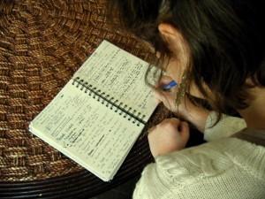 1. Réflexions et questions<br />Nous entrons dans le vif du sujet. Cette photo met en avant deux éléments: le carnet de recherche et Sophie. En pleine réflexion, nous avons construit une grille d'interview pour notre témoin et notre expert. Nous avons mis sur papier une série de questions afin d'être claires et précises. La photo retranscrit ce moment d'écriture. Sophie est au premier plan, la tête légèrement penchée en avant sur son carnet d'écriture. Cet élément se détache des autres par sa bichromie. L'œil est ainsi attiré par l'objet qui est au centre de l'image. Dans le carnet se trouve l'ensemble des questions que nous poserons à Céline Pérra et Pascal Laurent. Sur la page de gauche se trouve la grille correspondant à Pascal Laurent, et sur la page de droite celle correspondant à Céline Pérra. Les questions ne sont évidemment pas les même pour nos deux personnages. Nous avons choisi d'interroger Pascal sur la construction d'un décor en général, tandis qu'avec Céline Pérra nous nous intéressons plus précisément à la pièce de Fréderic Elkaïm.<br />Dans cette image, le photographe s'efface derrière Sophie. En se positionnant dans son dos, nous souhaitions que le spectateur se place dans la tête de Sophie, tout en gardant une certaine distance avec elle. Ainsi, nous assistons à la scène tout en préservant l'intimité du personnage.